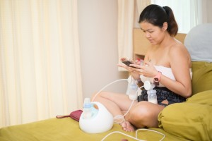 Mother doing breast feeding electronic for her baby milk stock