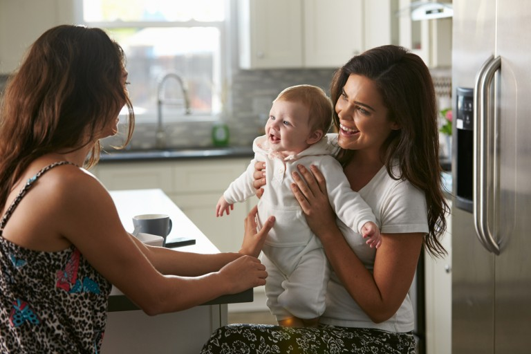 Female couple sitting in the kitchen holding their baby girl