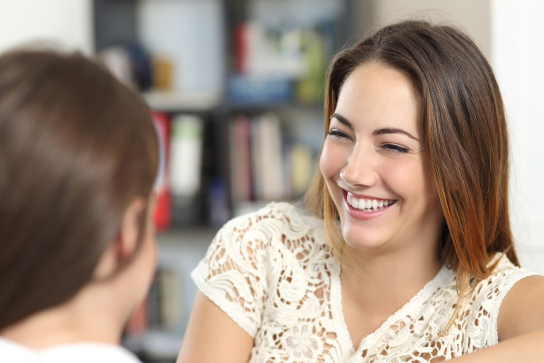 Happy woman talking and laughing with a friend at home