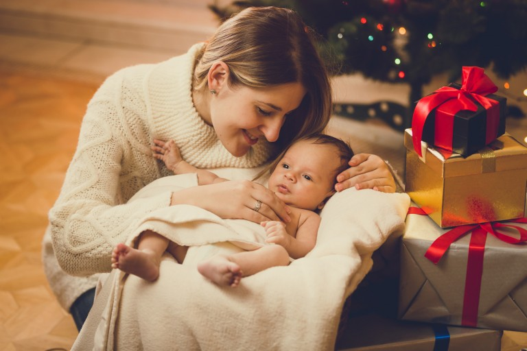 mother kissing baby boy lying in living room decorated for Chris